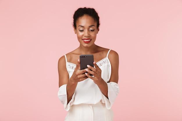 휴대 전화를 사용 하여 분홍색 backgroung 벽에 고립 된 아름 다운 젊은 아프리카 여자