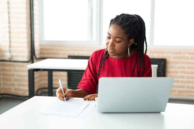 Beautiful young african woman in office with laptop