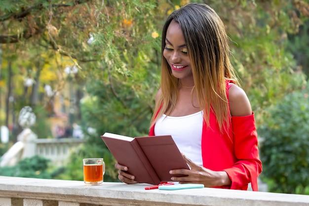 秋の本を読んで美しい若いアフリカの女性は公園で背景を残します