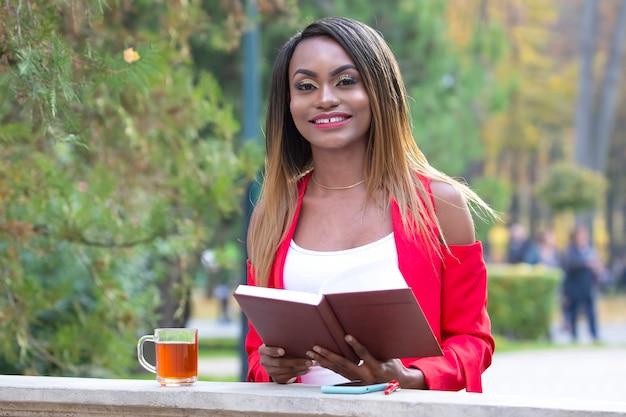 Красивая молодая африканская женщина, читающая книгу на поверхности осенних листьев в парке