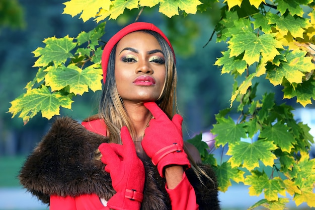 Beautiful young african woman in red on autumn leaves