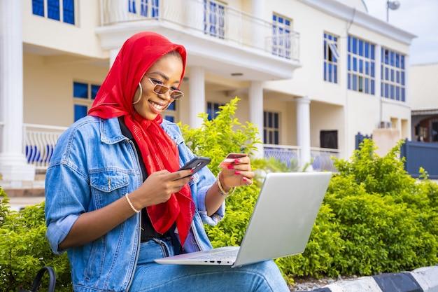 外で彼女のラップトップを使用しながら笑っている美しい若いアフリカの女性