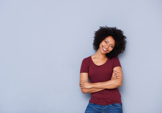 Beautiful young african woman standing against gray background with arms crossed