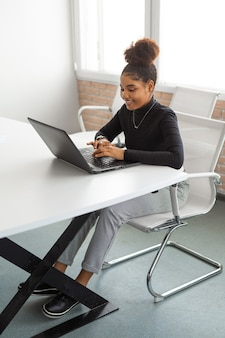 Beautiful young african woman at the table with laptop