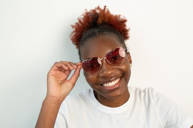 サングラスオリジナルメガネをかけている美しい若いアフリカの女性