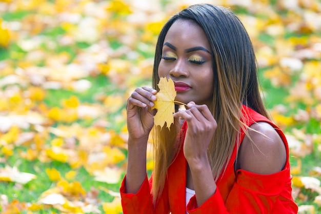 Красивая молодая африканская женщина с осенним листом в руках