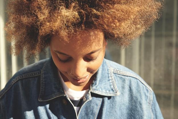 巻き毛と灰色の壁で屋外でポーズ健康的なきれいな肌と美しい若いアフリカ人女性