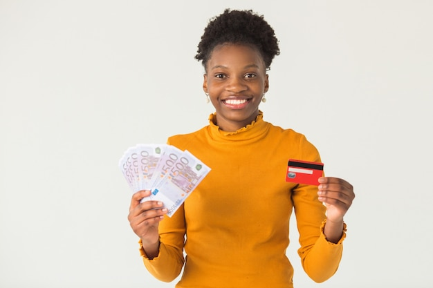 Beautiful young african woman with euro and credit card in her hands