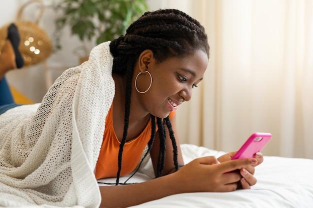携帯電話を持つ美しい若いアフリカの女性はベッドに横たわっています
