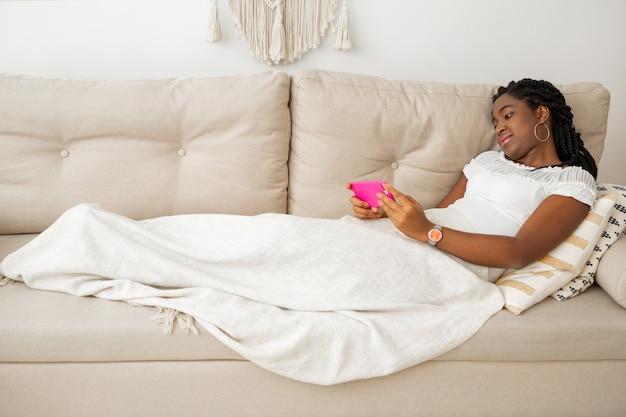 Красивая молодая африканская женщина с мобильным телефоном лежит на диване