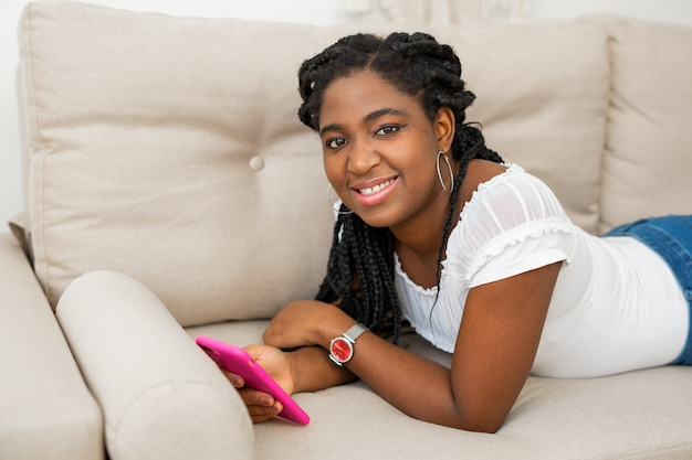 Beautiful young african woman with mobile phone lies on the sofa