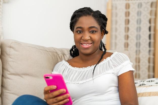 Красивая молодая африканская женщина с мобильным телефоном на диване