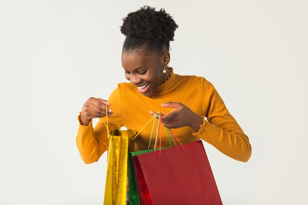 Beautiful young african woman with packages in her hands