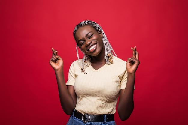 Красивая молодая афро-американская женщина держит пальцы скрещенными и улыбается, изолированные на красном фоне