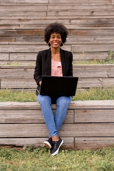 Beautiful young afro american woman using laptop, sitting on wood stairs and smiling. wood background. lifestyle outdoors