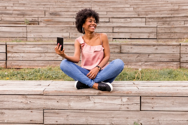 Beautiful young afro american woman using mobile phone, sitting on wood stairs and smiling. wood background. lifestyle outdoors