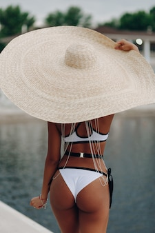Beautiful young afro woman in bikini relaxing near swimming pool wearing big straw hat.