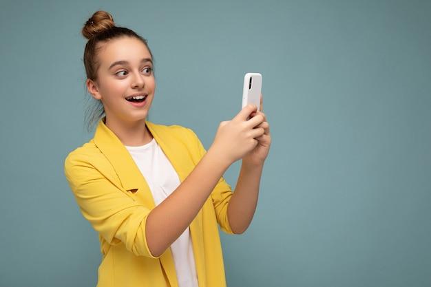 노란색 재킷과 흰색 티셔츠를 입고 파란색 위에 고립된 아름다운 젊은 놀란 소녀