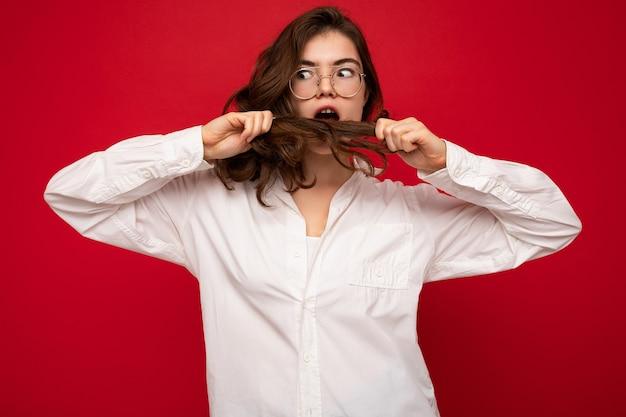 白いシャツと光学メガネを身に着けている美しい若い驚いたショックを受けたブルネットの女性セクシーな屈託のない
