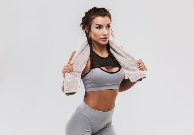 Красивая молодая удивительная сильная спортивная фитнес-женщина позирует на белом фоне стены