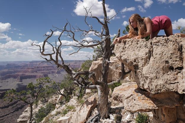 赤い岩の砂漠で白い笑顔を着ている美しい若いアメリカ人の女の子モデル。セレクティブフォーカス