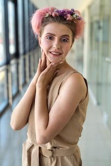 日光の下でポーズをとって春気分の美しく、若くてファッションの女性
