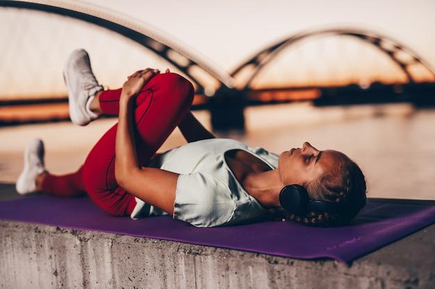 아름다운 젊고 건강한 여성은 도시 다리 거리에서 혼자 운동을 합니다. 그녀는 헤드폰으로 음악을 듣습니다. 백그라운드에서 아름 다운 석양입니다.