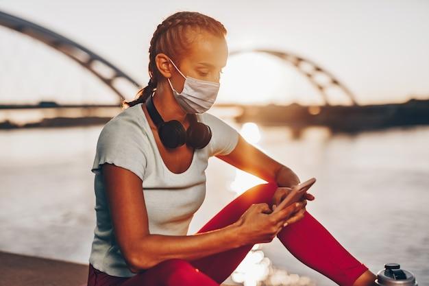 아름다운 젊고 건강한 여성은 도시 다리 거리에서 혼자 운동을 합니다. 그녀는 바이러스나 알레르기 감염으로부터 자신을 보호하기 위해 보호용 안면 마스크를 쓰고 있습니다. 백그라운드에서 일몰입니다.