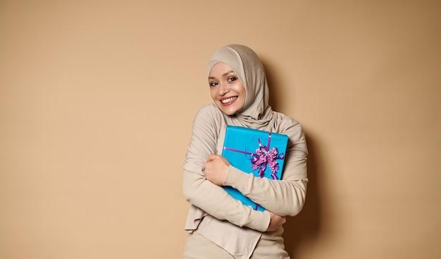아름 다운 젊은 아랍 이슬람 여자 선물을 포옹 하 고 카메라에 함박 웃음으로 귀 엽 고 웃 고.