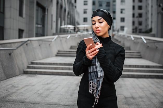 아름 다운 젊은 아라비아 여자 스탠드와 전화를 봐.