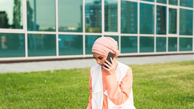 Красивая молодая арабская женщина разговаривает по мобильному телефону