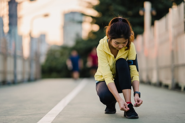 Beautiful young asia athlete lady exercises tying laces for work out in urban environment. japanese teen girl wearing sport clothes on walkway bridge in early morning. lifestyle active sporty in city.