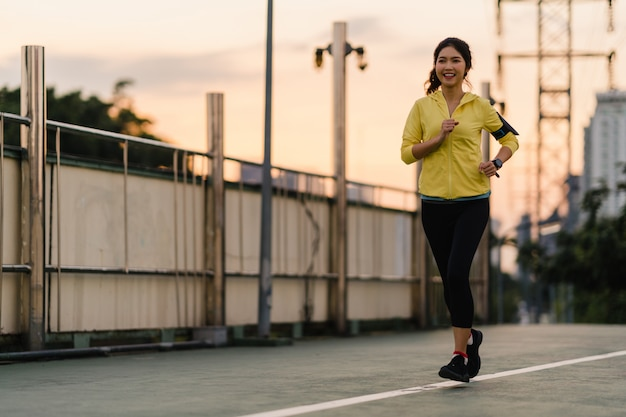 Beautiful young asia athlete lady running exercises work out in urban environment. japanese teen girl wearing sports clothes on walkway bridge in early morning. lifestyle active sporty in city.