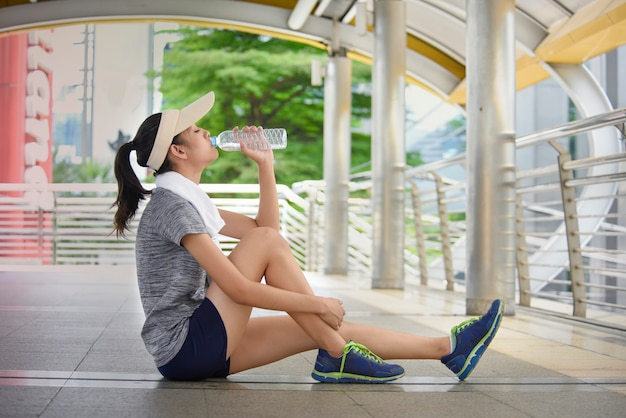 Beautiful young asia woman drinking water after training.