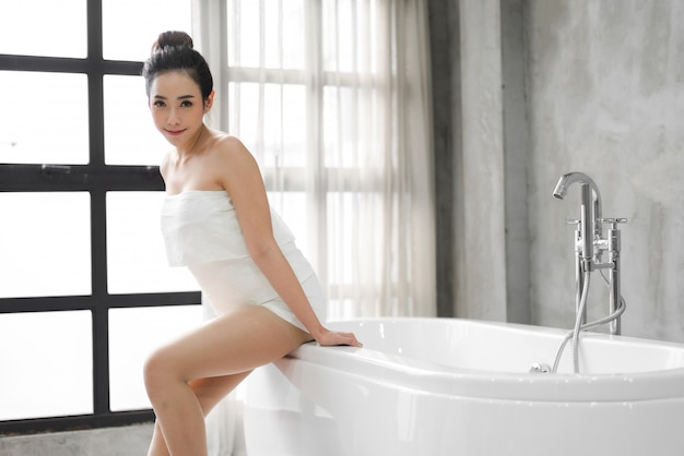 Beautiful young asia woman enjoy relaxing sitting on bathtub at the bathroom