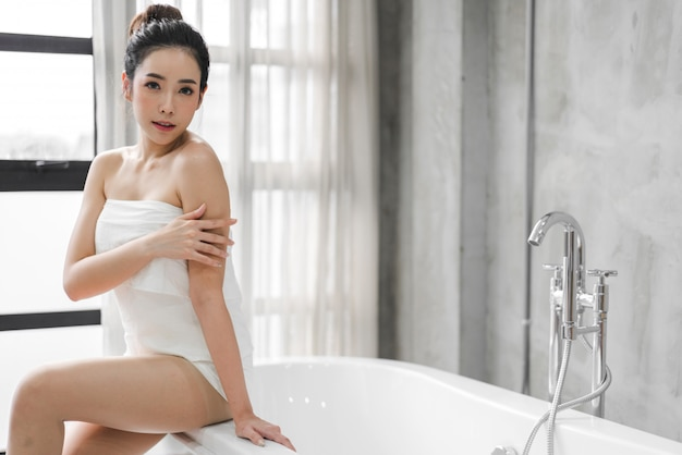 Beautiful young asia woman enjoy relaxing taking a bath on bathtub at the bathroom
