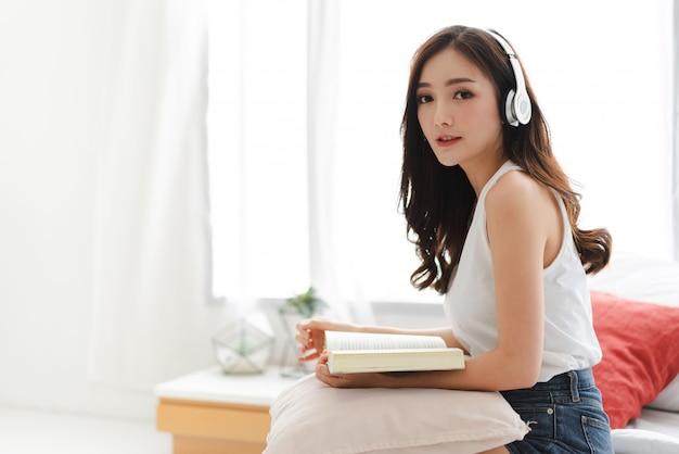 自宅のベッドにヘッドフォンで音楽を聴いてリラックスできる美しい若いアジア女性