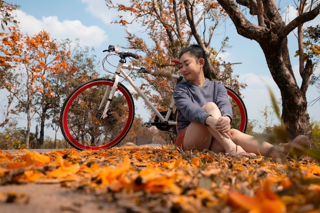 Beautiful young asia woman sitting next to her bike outdoors at palash tree with full of beautiful orange flower background