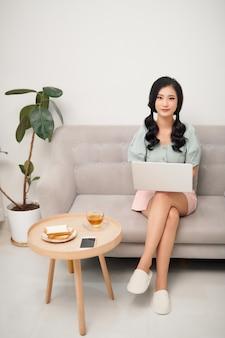 リビングルームでラップトップで働く美しい若いアジアの女性