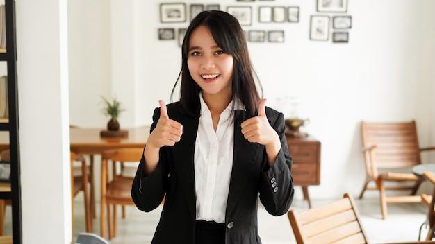 사무실에서 양복과 괜 찮 아 요 손가락 손에 아름 다운 젊은 아시아 비즈니스 여자