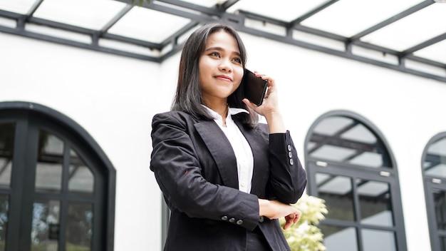 전화 및 갈색 봉투로 전화하는 카페에 서있는 소송에서 아름 다운 젊은 아시아 비즈니스 여자