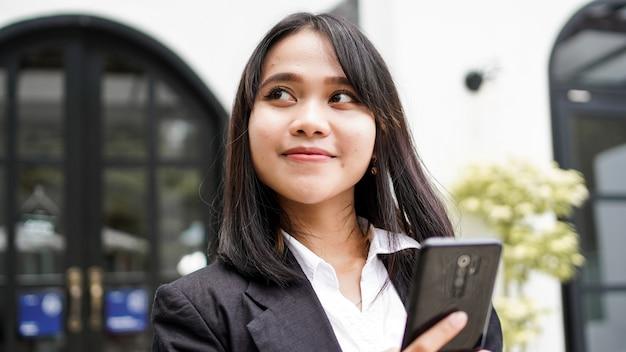 전화 및 갈색 봉투와 함께 카페에 서 정장에 아름 다운 젊은 아시아 비즈니스 여자