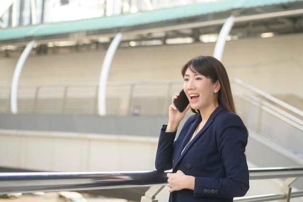 美しい若いアジアのビジネス女性は、現代の都市でスマートフォンを使用しています