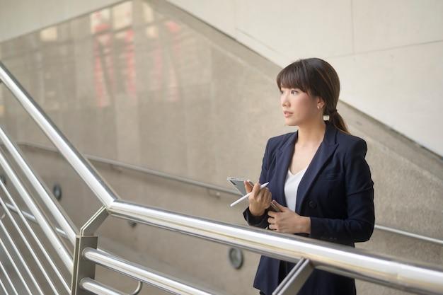 Красивая молодая азиатская бизнес-леди использует таблетку в современном городе Premium Фотографии