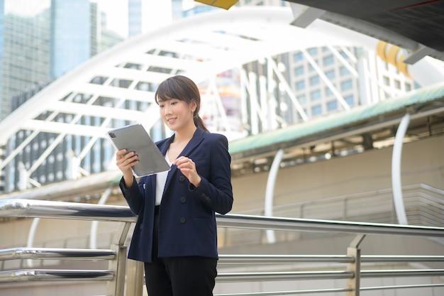 Красивая молодая азиатская бизнес-леди использует таблетку в современном городе