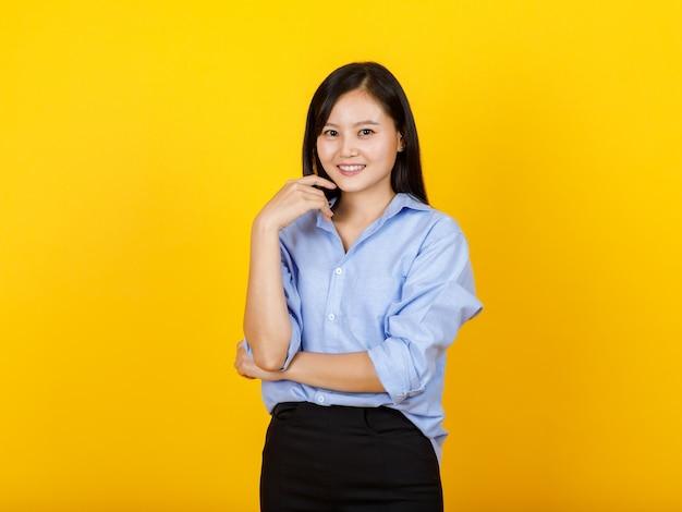 아름다운 젊은 아시아 여성 비서는 긴 소매 셔츠의 스마트한 임원 드레스 스타일로 웃고 있고 매력적인 외딴 패션 초상화를 위해 팔짱을 끼고 긴장을 푸는 것을 기쁘게 생각합니다.