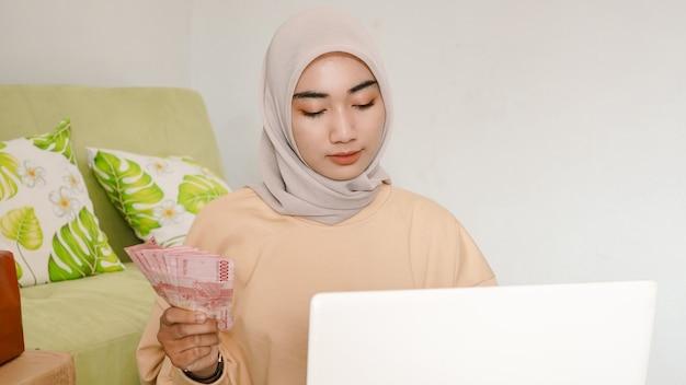 注文収入を計算する美しい若いアジアの実業家