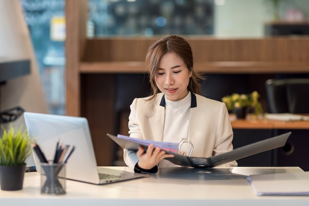 Beautiful young asian businesswoman holding documents to checking authenticity the laptop is placed at the office table.