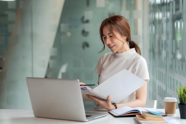 노트북의 진위 여부를 확인하기 위해 문서를 들고 있는 아름다운 젊은 아시아 여성 사업가가 사무실 테이블에 놓여 있습니다.