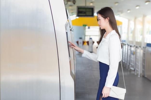 흰 셔츠를 입은 아름다운 젊은 아시아 여성 사업가가 사무실에 출근하기 위해 하늘 기차역에 있는 매표기를 누르기 위해 서 있습니다.